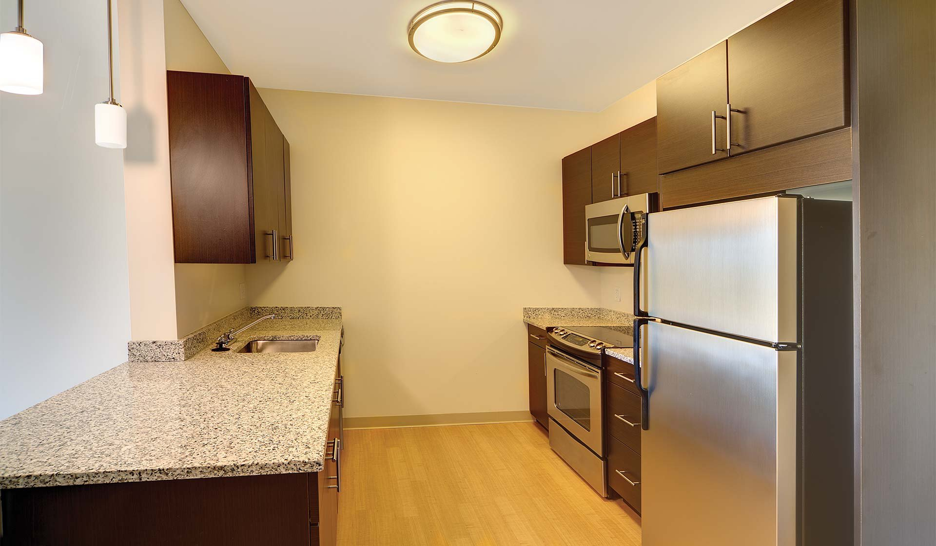 Charles Bank Apartments - modern kitchen with dark wood cabinets and stainless steel appliances - Waterown, massachusetts